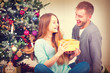 Happy Couple with Christmas Gift at Home. Christmas Celebration