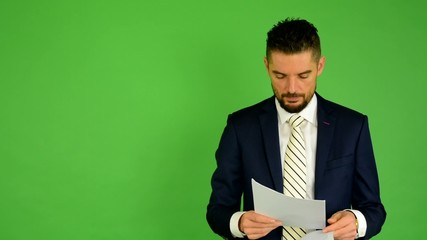 business man looks papers - green screen - studio