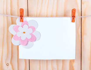 paper flower attached to the card on a wooden background
