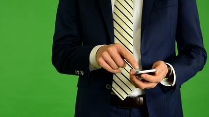 business man works on phone - green screen - studio - closeup