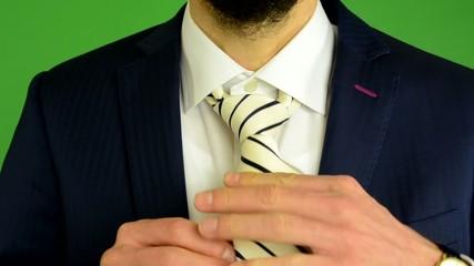 business man adjusts his tie - green screen - studio - closeup
