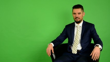 business man sits and talks to camera (interview) - green screen