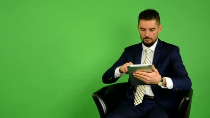 business man sits and works on tablet and smiles - green screen