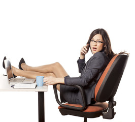 worried businesswoman with feet on desk talking on the phone