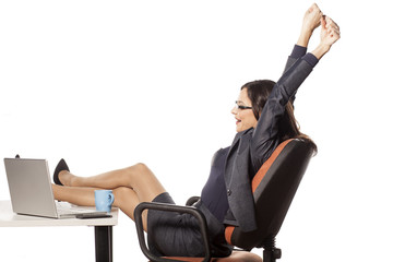 young businesswoman with legs on the table stretches her hands