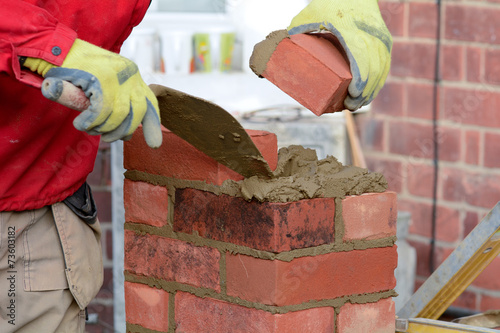 Fotobehang Wand Bricklaying - laying a brick