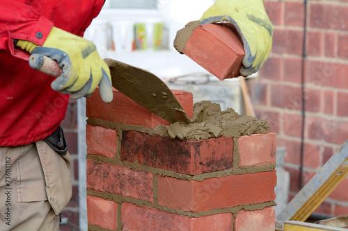 Bricklaying - laying a brick - 73603182