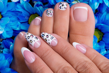 woman's nails of hands and legs with french manicure