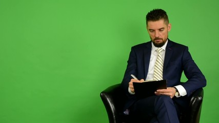 business man sits and writes to paper, smiles - green screen