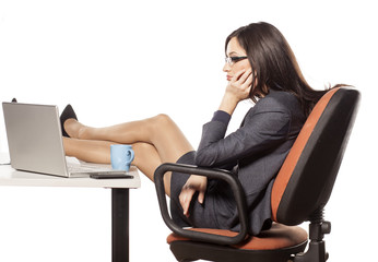 Bored young businesswoman with her legs on the table