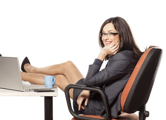 Smiling young businesswoman with her legs on the table