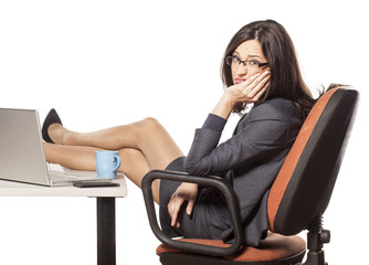 unhappy young businesswoman with her legs on the table
