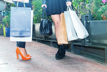 Two girls outdoor shopping. Detail on legs and bags