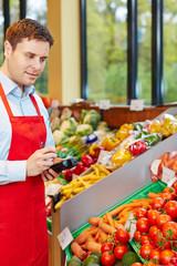 Mann im Biomarkt bestellt frisches Gemüse