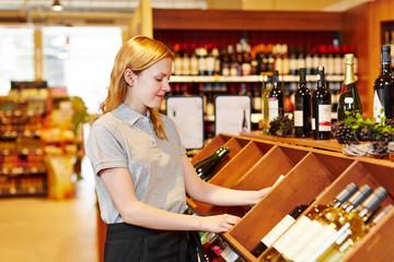 Verkäuferin im Supermarkt räumt Wein ein