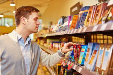 Mann kauft Schokolade im Supermarkt