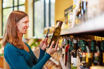 Frau scannt Flasche Olivenöl mit Smartphone