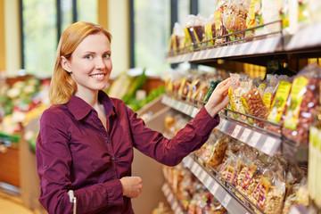 Junge Frau kauft Nüsse im Supermarkt