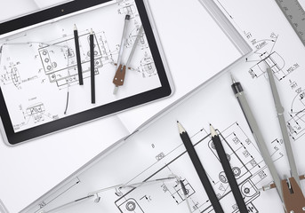 Tablet pc lying on open enpty book and engineering drawings.