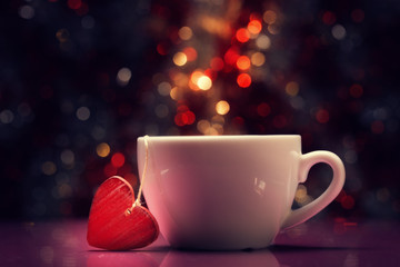 Cup with red heart against defocused lights.