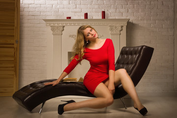 Beautiful lady in a red dress sitting on the couch