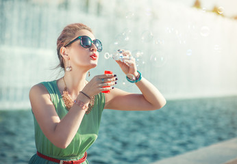 Beautiful girl in vintage clothing blowing bubbles