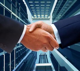 Contractors handshake on a skyscraper background