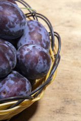 plums in a basket on a wooden background