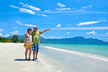 Romantic Senior Couple Walking On Beautiful Tropical Beach.