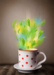 Tea cup with leaves and colorful abstract lights