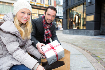 Young attractive couple putting gift in bags