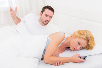 Young couple arguing on a bed cause of texts