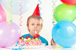 Little cute boy in holiday hat with birthday cake with whistle