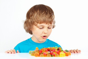 Child with colored jelly candies on a white background