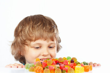 Little boy with jelly candies on a white background