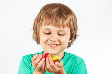 Little boy with sweets and candies on a white background