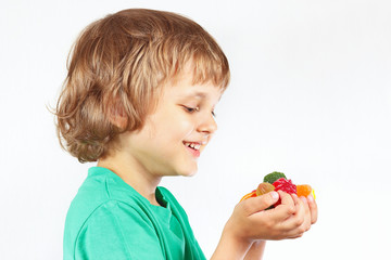Little child with colored sweets and jelly candies