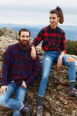 Beautiful couple of hikers resting sitting on mountain hill
