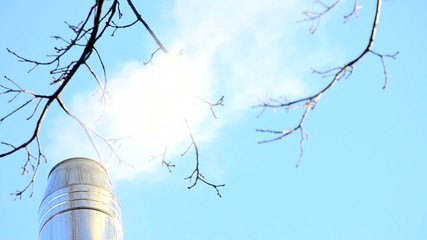 White smoke from stainless steel chimney on sky background