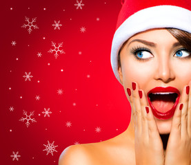 Christmas Woman. Beauty Model Girl in Santa Hat over Red