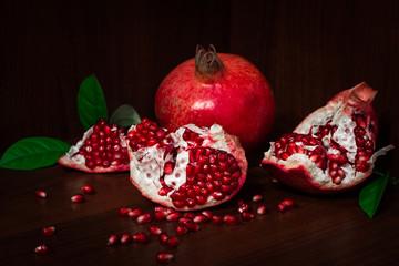 Pomegranate with broken segments, still life on dark background