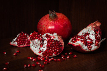 Pomegranate with broken segments, still life on dark background