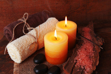 Spa stones with candles and sea salt on wooden background