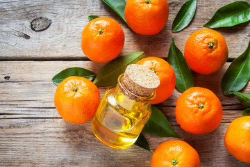 Tangerines with leaves and bottle of essential citrus oil on a w