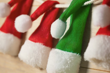 One green santa hat among of three red. Shallow depth of field,
