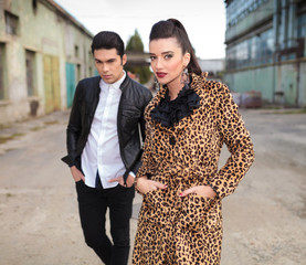 Fashion couple posing near old factory.