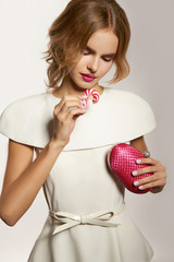 Beautiful girl in evening dress with candy and small bag