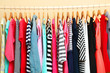 Colorful clothes on hangers in room - 73619914