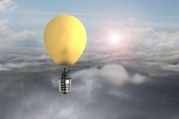 businessman in glowing yellow lightbulb hot air balloon flying