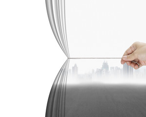hand pulling gray cityscape curtain revealing empty blank space